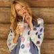 Frau in bunter Bluse mit Kaffee in der Hand.