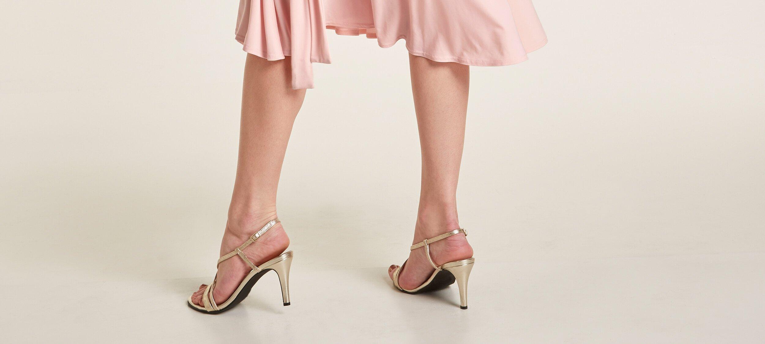 Frau trägt silberne Sandaletten.