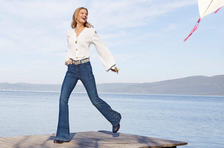 Frau mit weißer Bluse und Jeans.