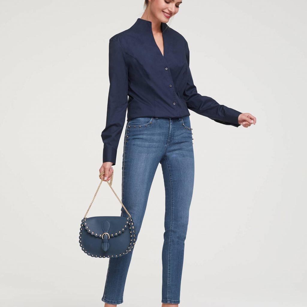 Frau bekleidet mit Bluejeans und schwarzer Bluse.