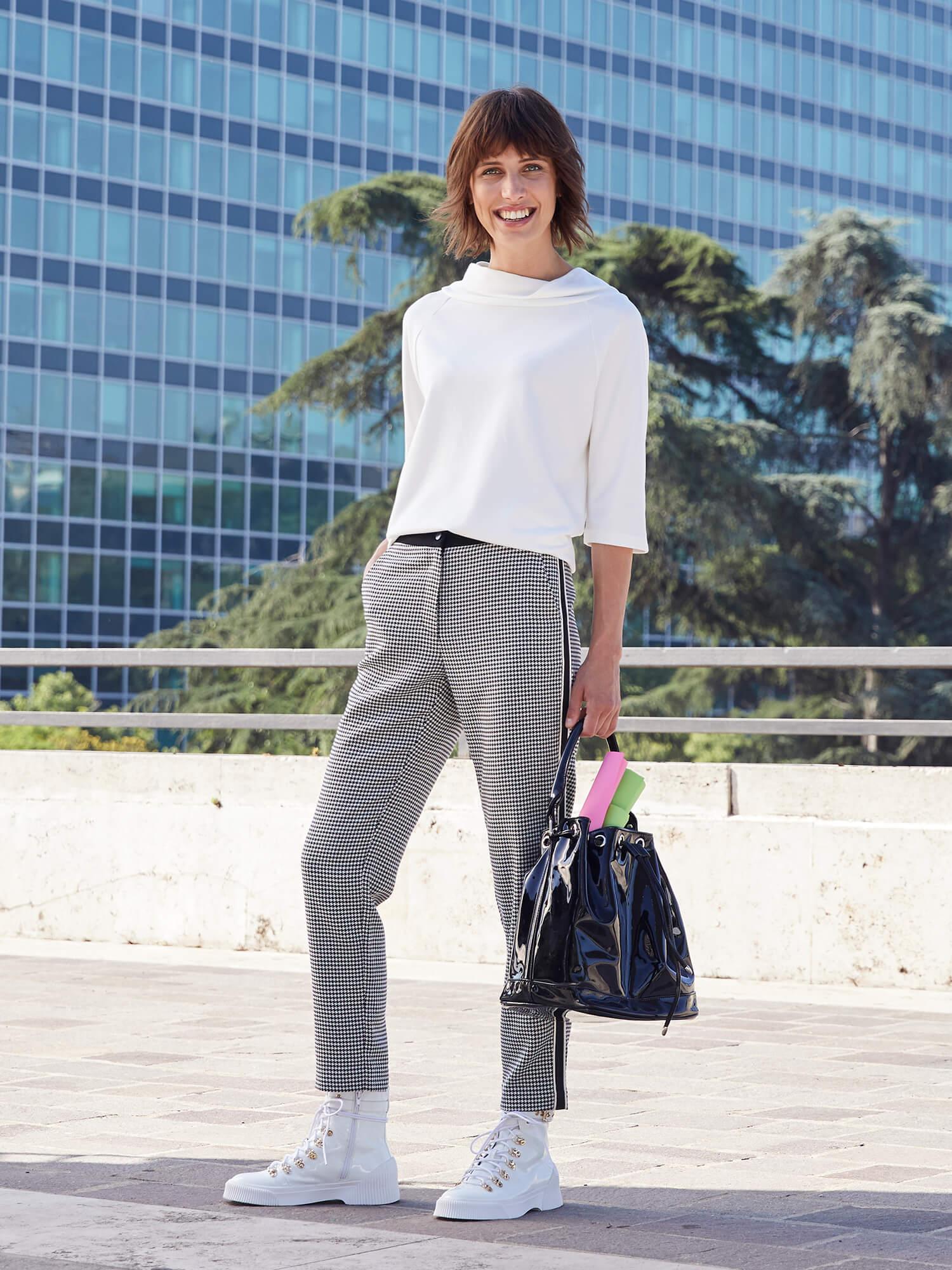 Frau mit weißem Shirt und grauer Hose.