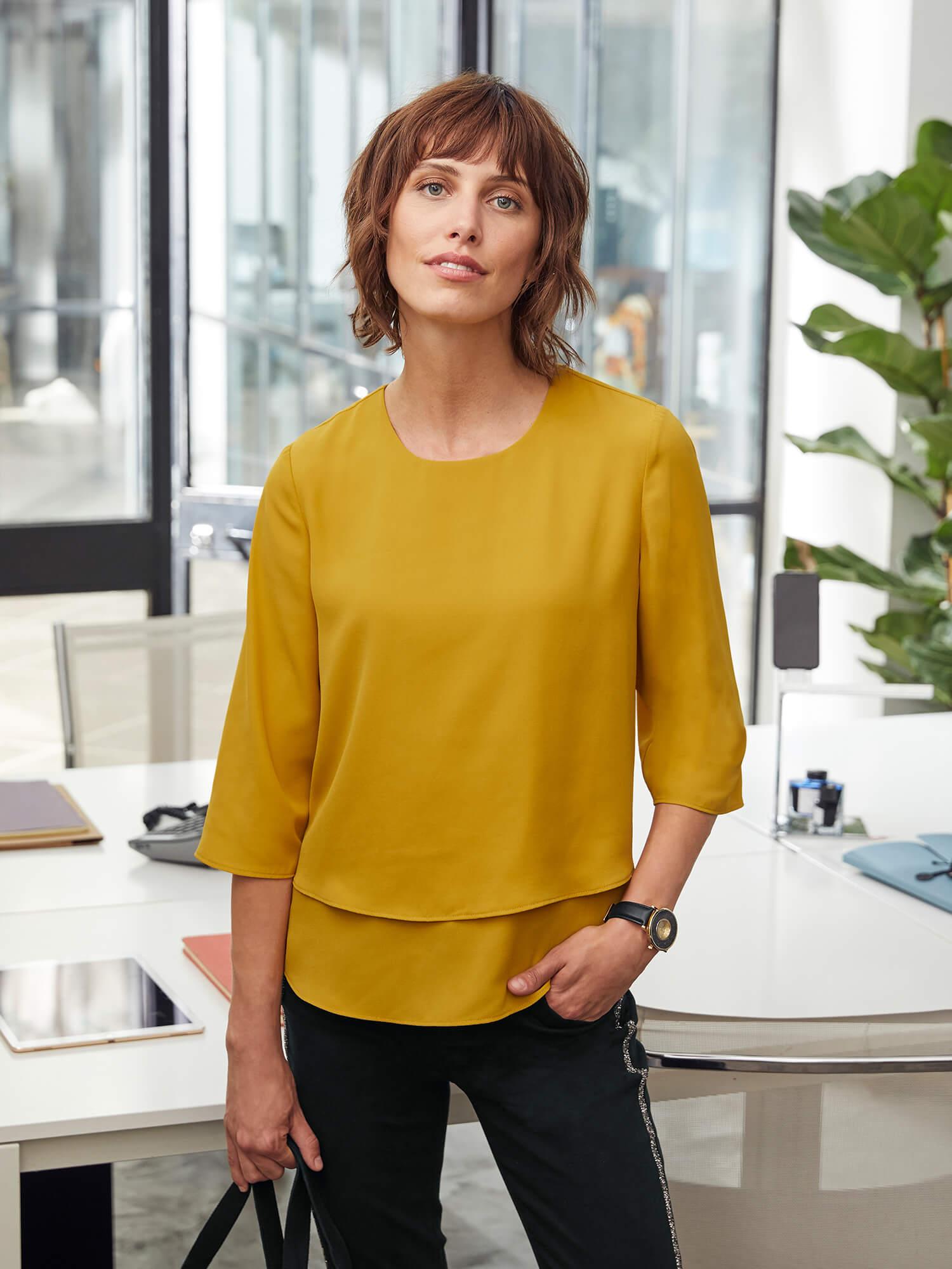 Frau mit gelber Bluse.
