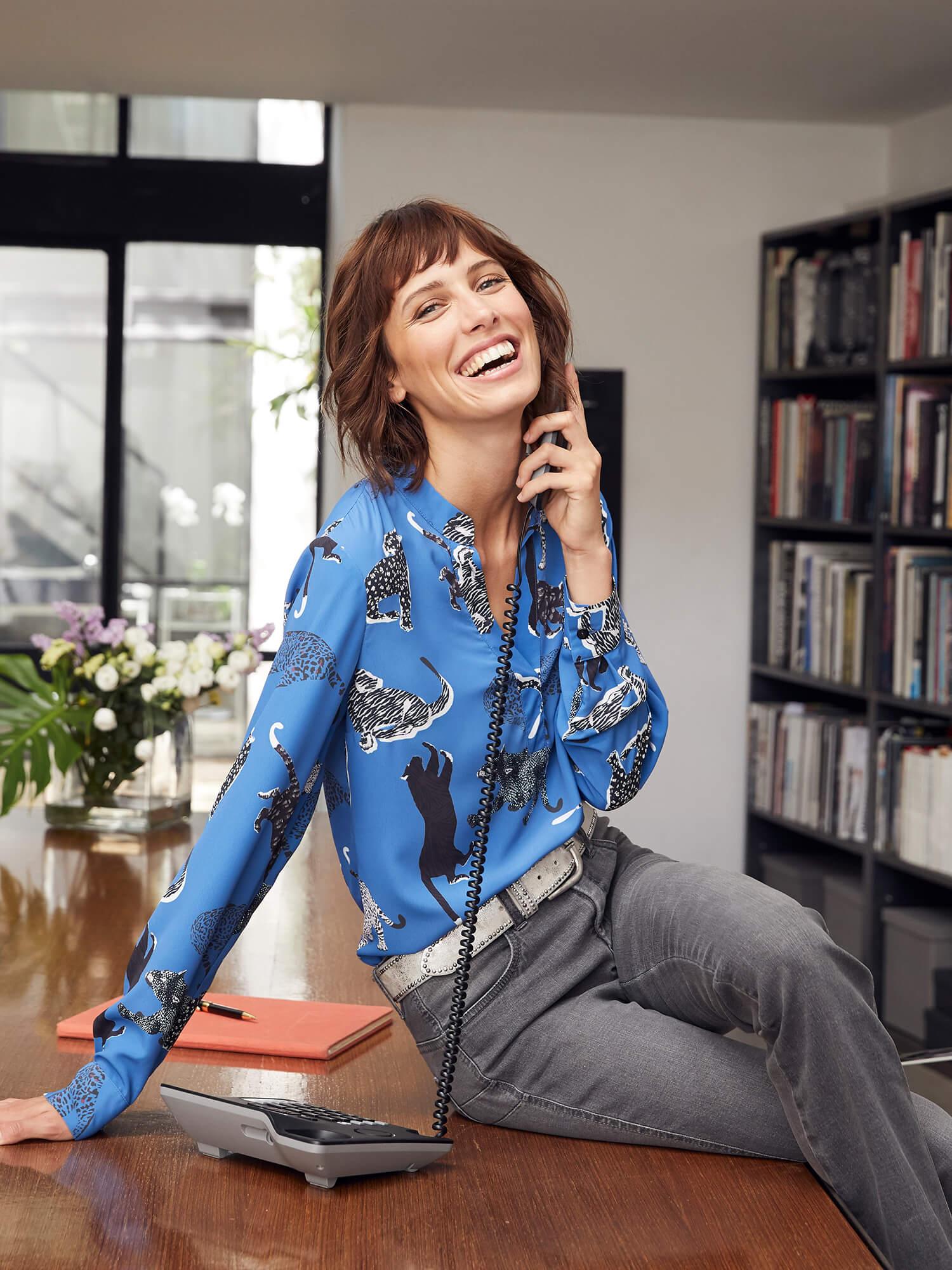 Frau mit blauer Bluse am Telefon.