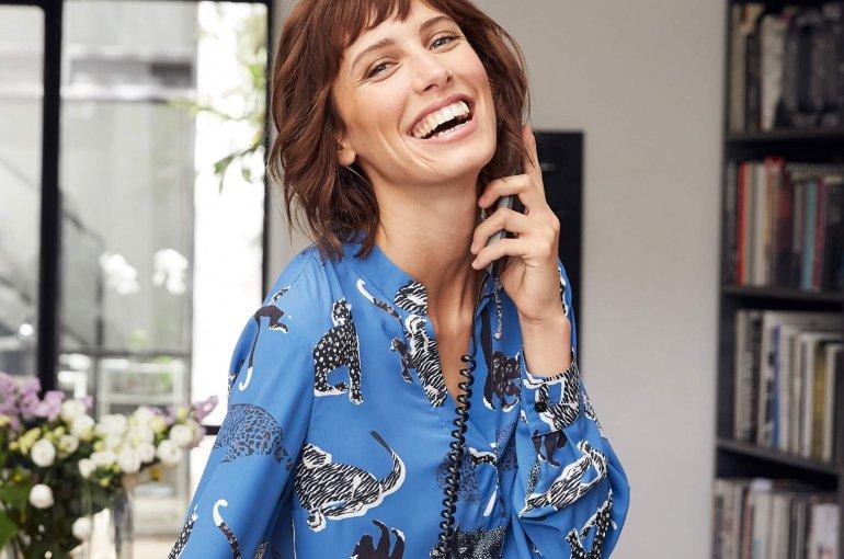 Lachende Frau mit blauer Druckbluse