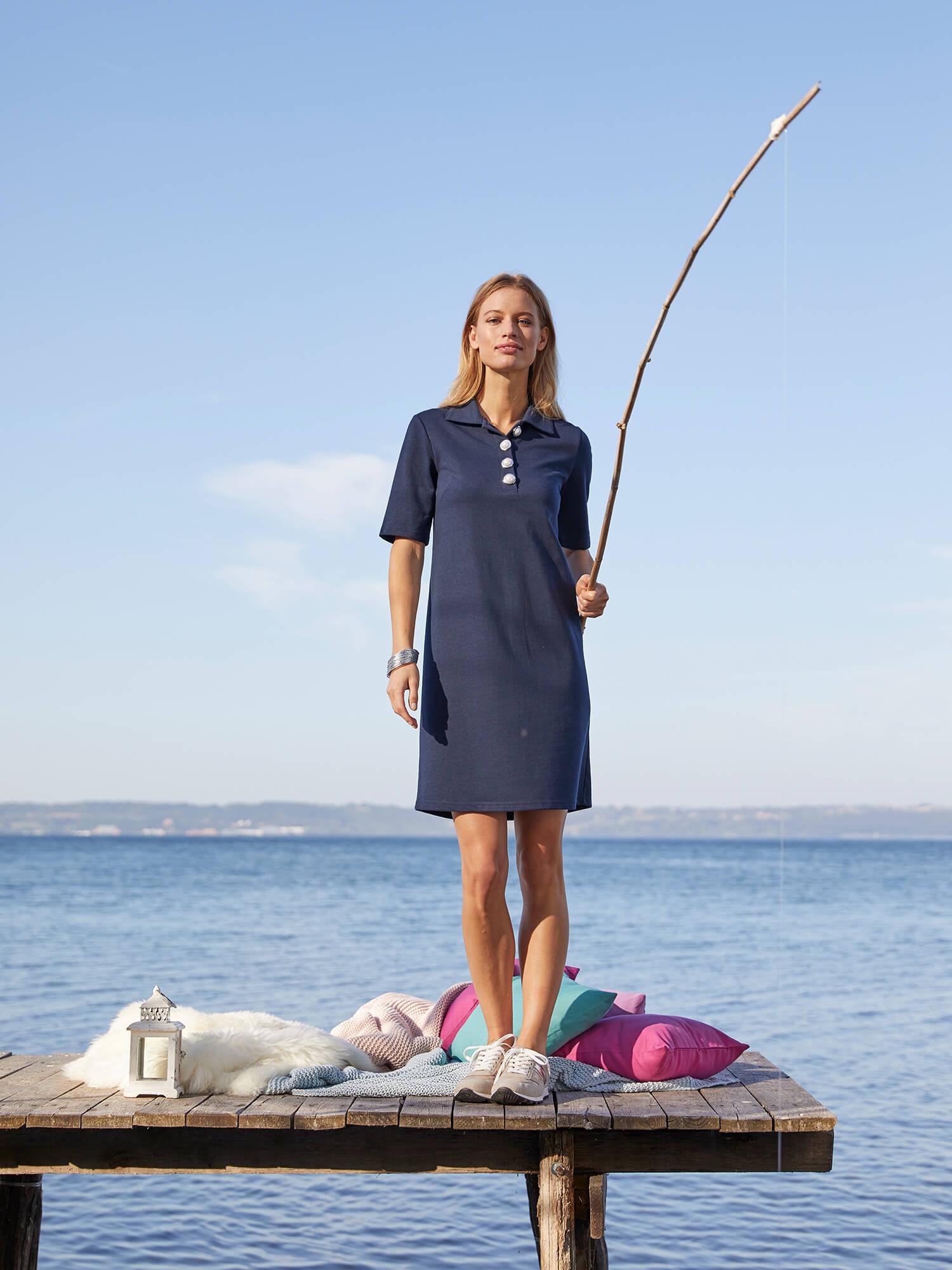 Frau in marinefarbenem Kleid am Meer.