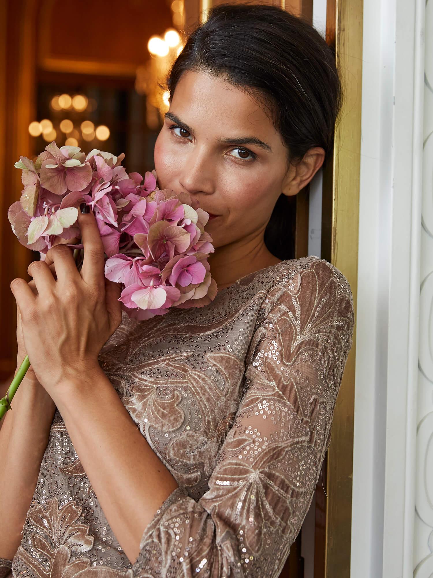 Frau die an Blumenstrauß riecht.
